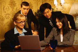 Business People Gathered Around Laptop